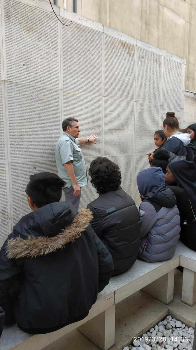 Le guide expliquant aux élèves l'importance du Mur des Noms